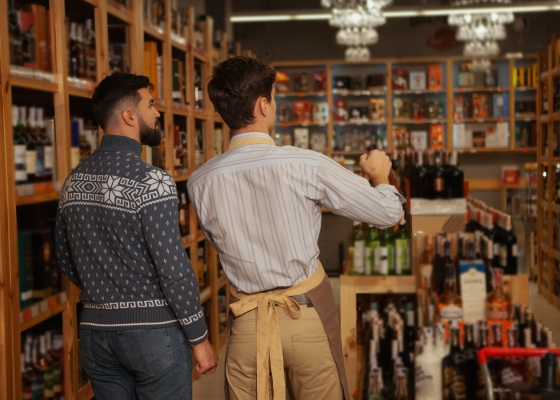 Liquor store owner helping his customer